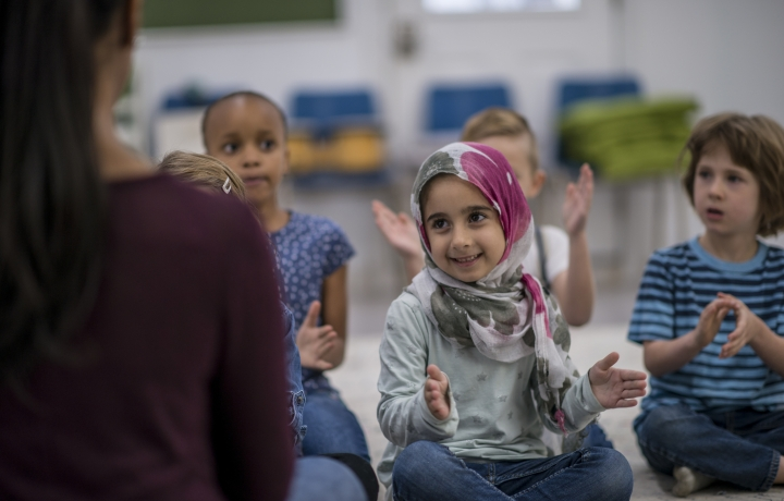Young children clapping along to a song