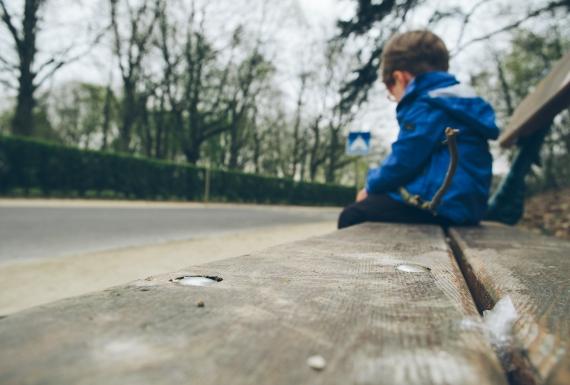 Sad boy sitting on a bark bench