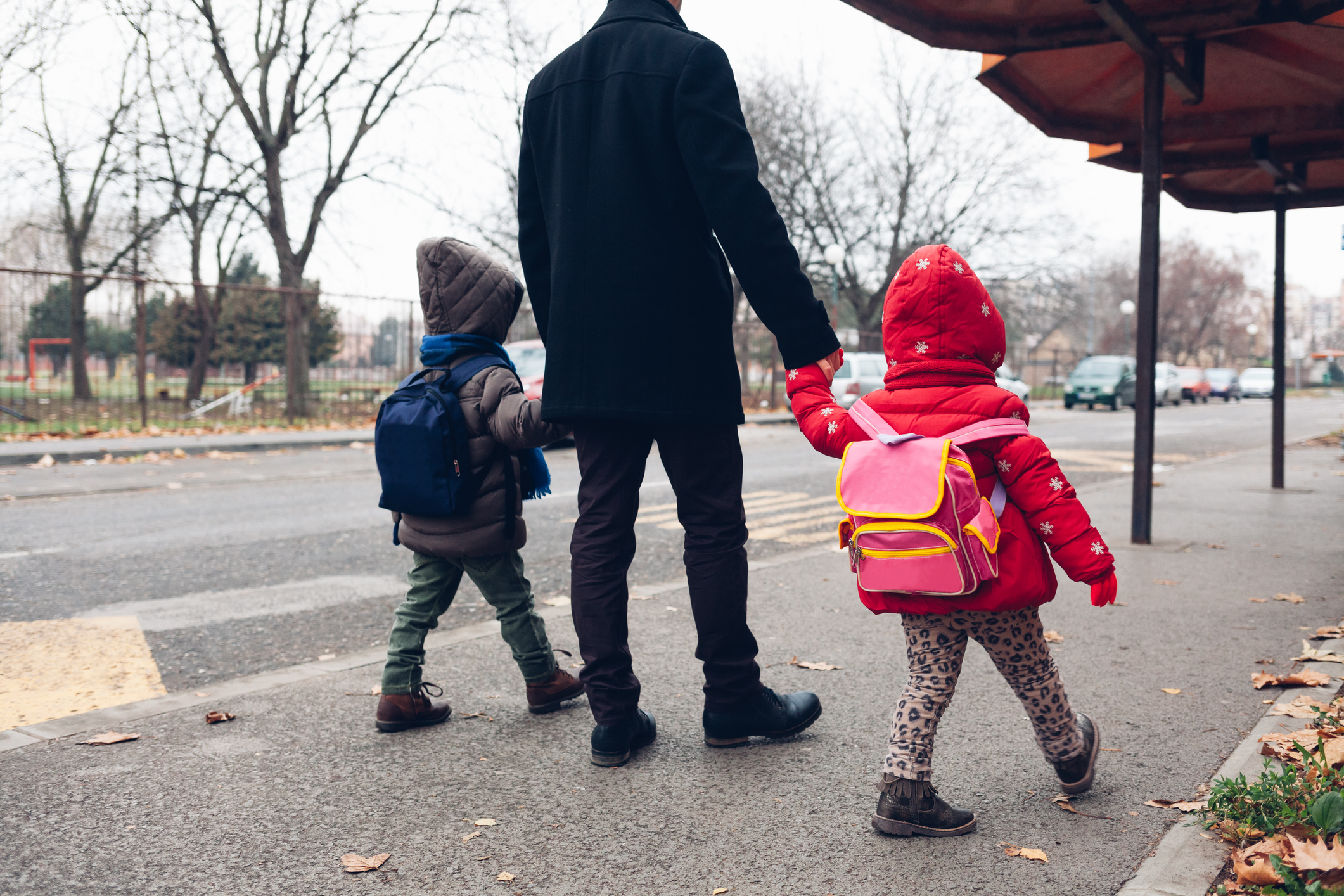 Dad with two children walking hand in hand to the bus stop